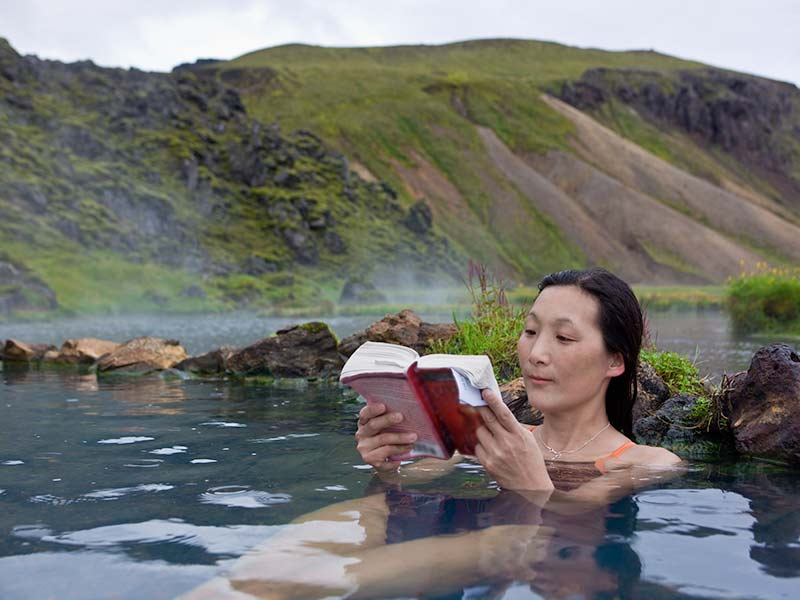Woman reading book in a hot spring
