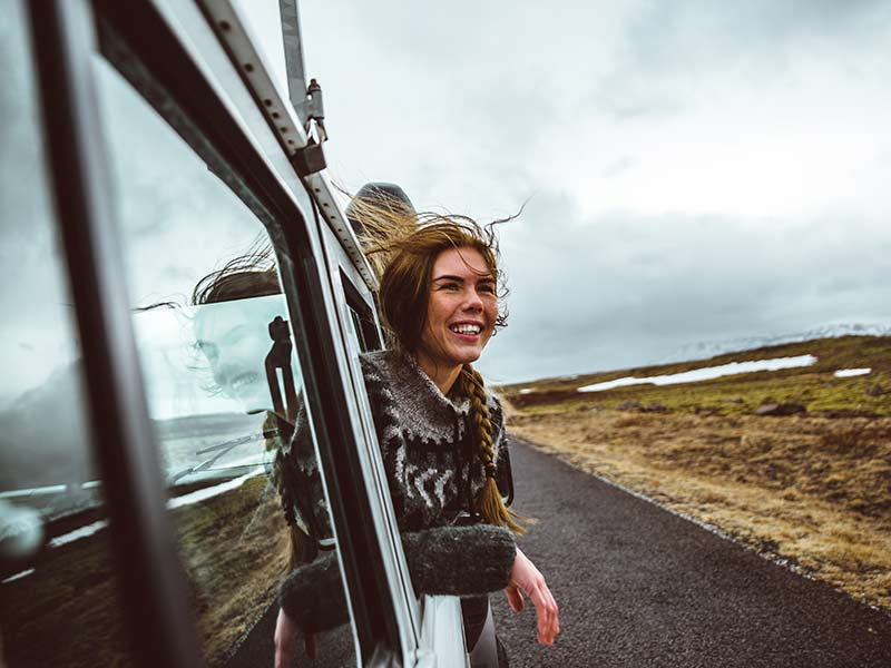 icelandic girl enjoying the landscape in Iceland from a car