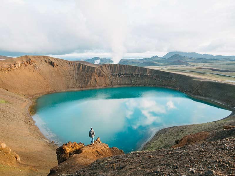 man looking at majestic volcanic lake in iceland, krafla, lake viti