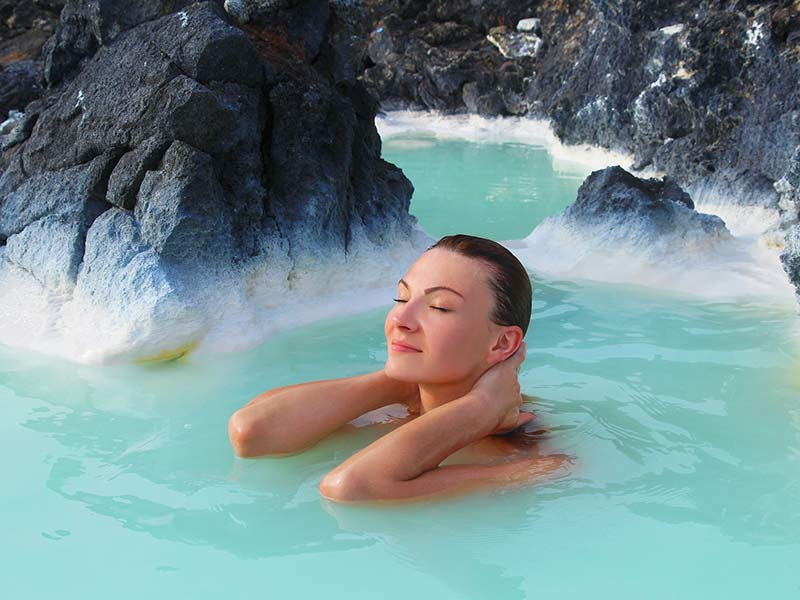 Young beautiful woman bathing in the blue lagoon