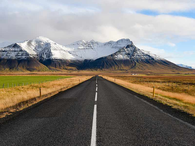 Road leading to snowcapped mountain in Iceland