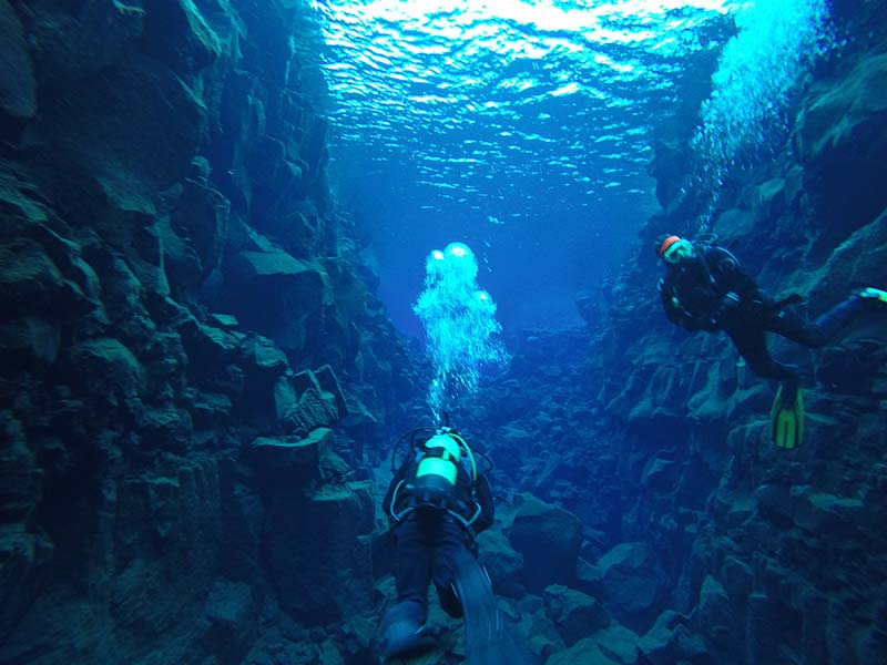 Two divers in the blue water in iceland
