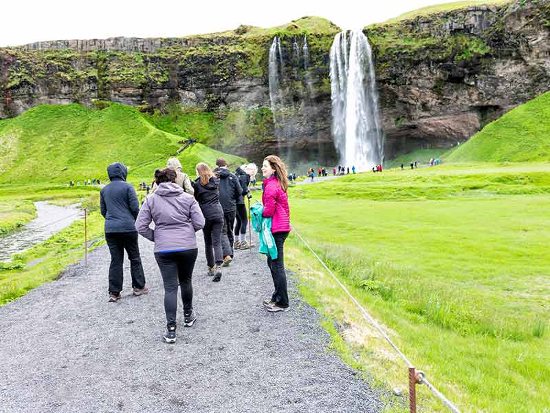 A group of people are heading to a waterfall in iceland