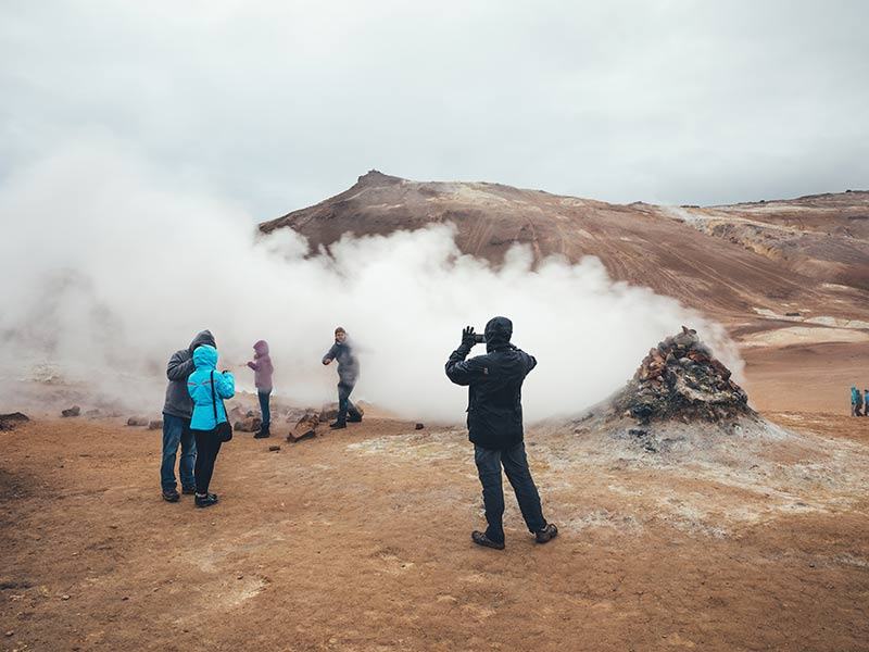 People taking pictures near a geothermal area In Iceland
