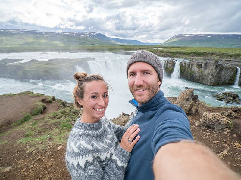 Couple taking selfie portrait with magnificent waterfall in Iceland