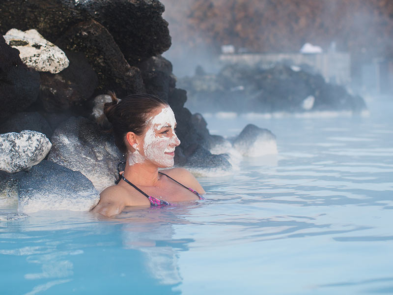 Woman relaxing in geothermal spa in hot spring pool in Iceland