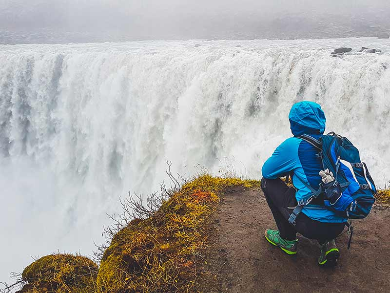 A man is looking at the Dettifoss waterfall near the ring road in Iceland