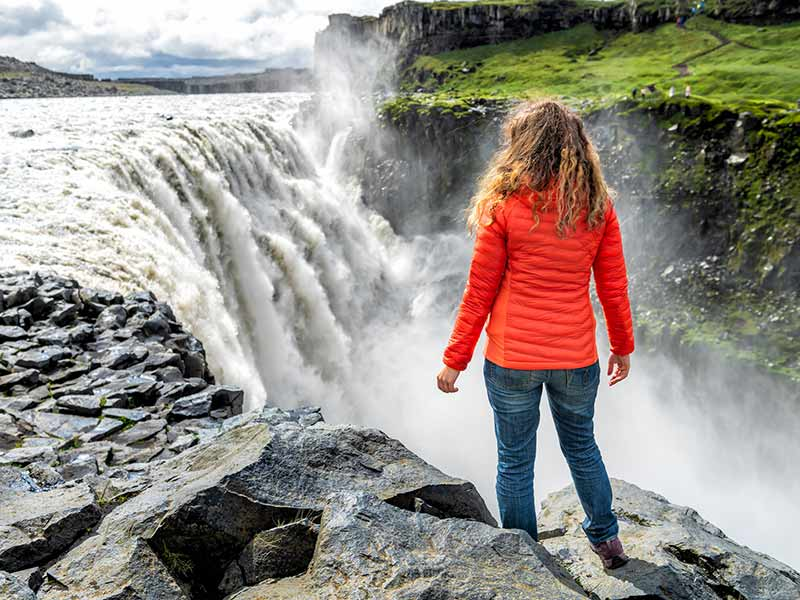 Woman watching Dettifoss waterfall on rocks water flowing mist spraying sunny day in Iceland
