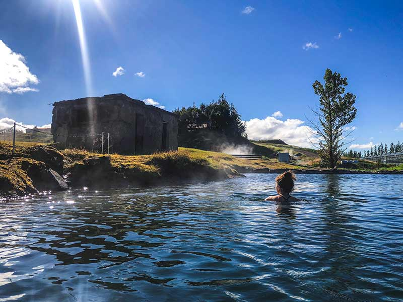 woman swimming in geothermal pool in fludir secret lagoon Iceland