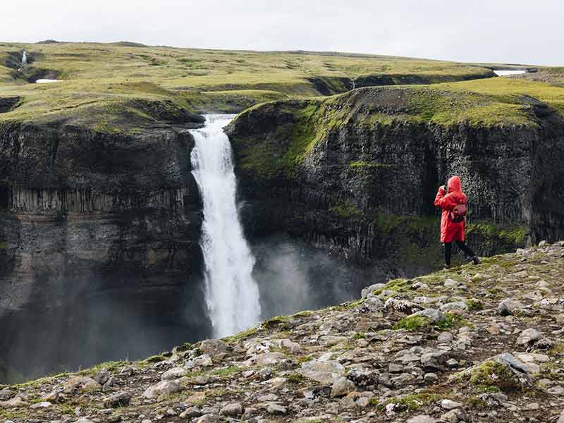 woman taking photo of Haifoss waterfall