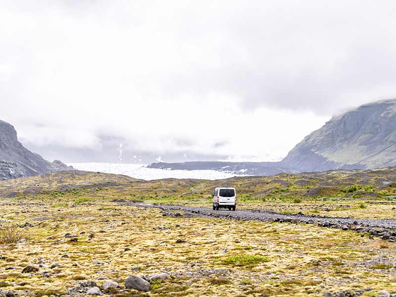 View on Iceland glacier tongues with tour van on gravel road, rocks, moss, fog, clouds, cliffs, mountains