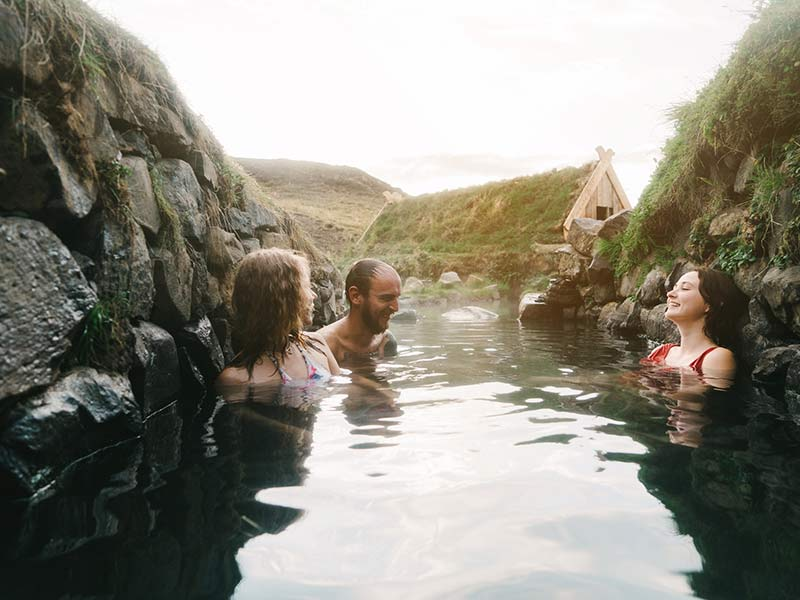 Friends taking bath in hot spring in Iceland