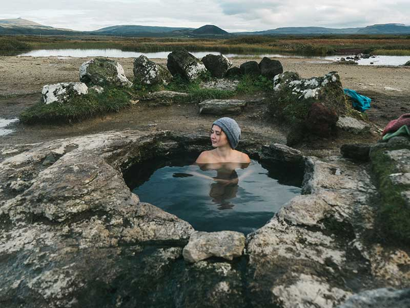 Woman swimming in hot pool in Iceland