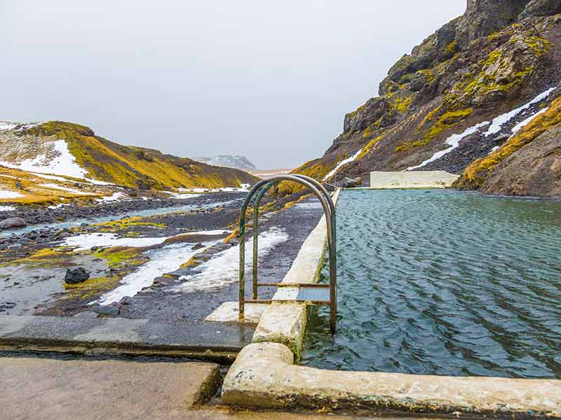 Natural swimming pool Seljavallalaug in iceland with man in water and snowy weather and mountains all around