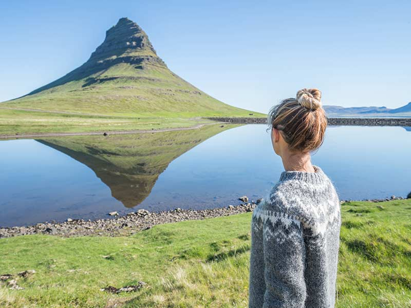 Young woman in Iceland contemplating famous Kirkjufell mountain