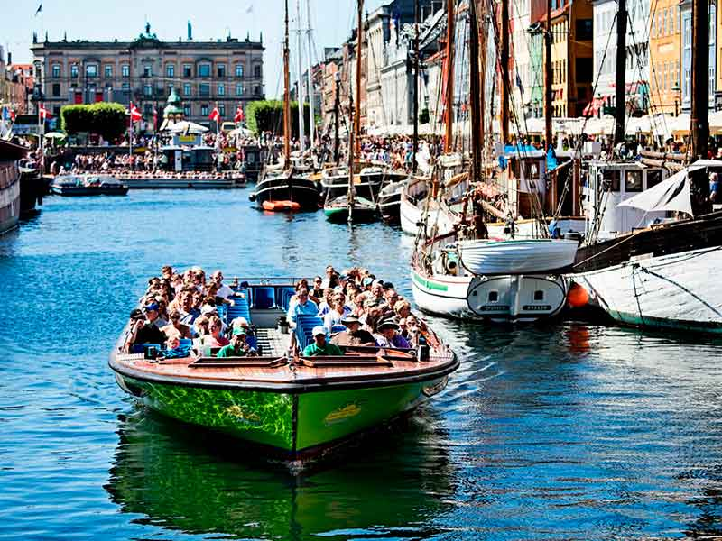 A group of tourists enjoy the tour through the canals in copenhagen