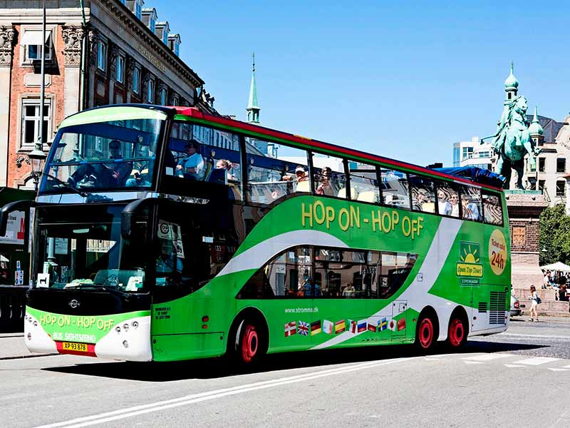 A double-decker hop on hop off bus drives around the streets of Copenhagen