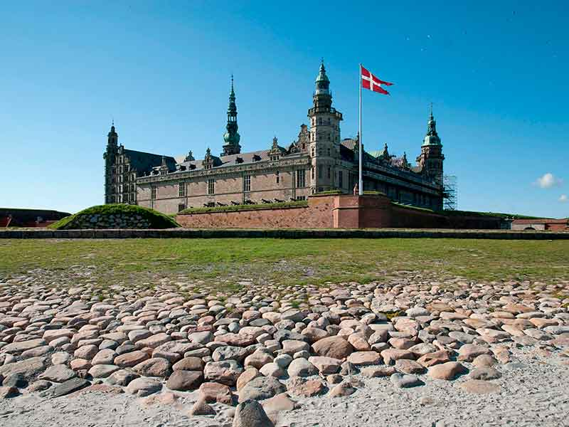 Beautiful castle with the Danish flag fluttering in front