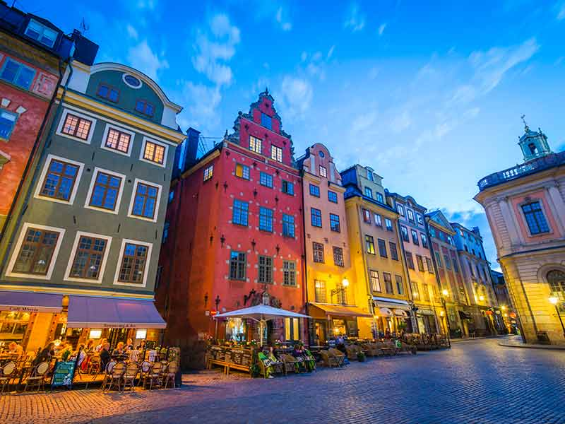 Stockholm tourists enjoying colourful Stortorget bars restaurants at sunset Sweden