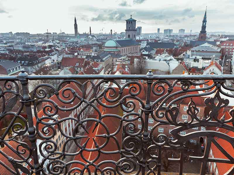Skyline of Copenhagen, Denmark with decorative fence, photo taken from The Round Tower, popular old city landmark and viewpoint