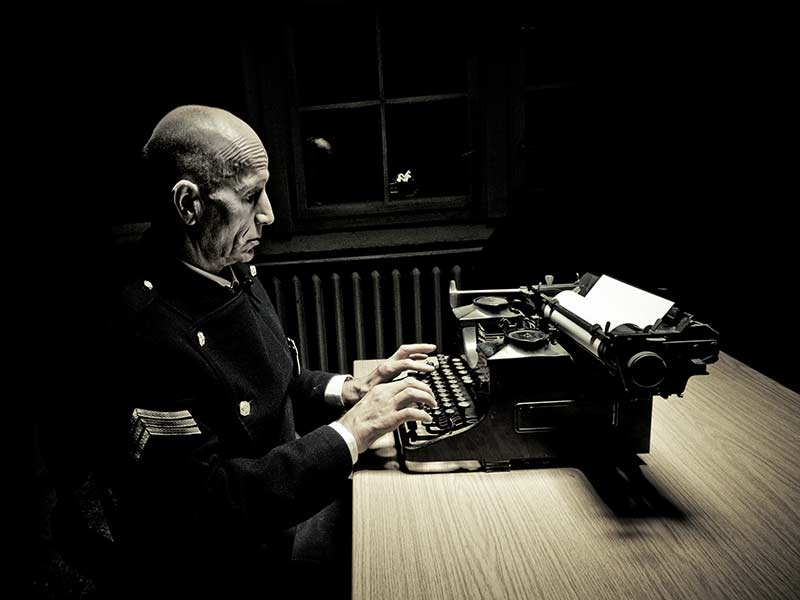 A KGB soldier writes on a typewriter