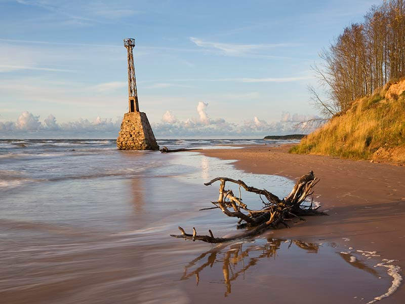 An old lighthouse on the shore of Vidzeme rocky beach near Kurmjrags