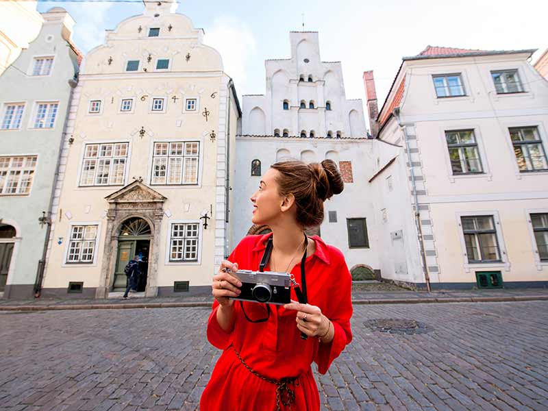 Portrait of a young female tourist with photo camera in front of the famous three brothers ancient houses in Riga.