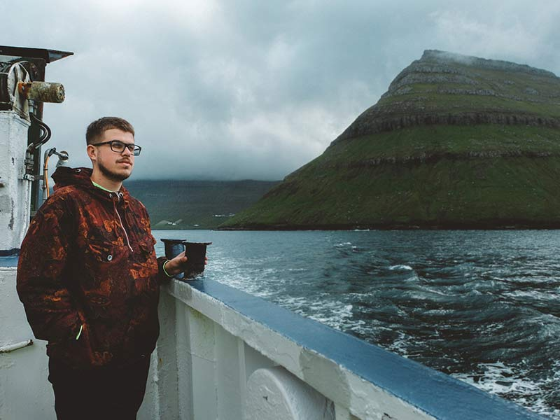 Man in ferry boat on the road to Kalsoy island on Faroe Islands